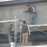 Four men on scaffolding applying Stucco to a Condo or Strata Property