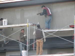 Four men on scaffolding applying Stucco to a Condo or Strata Property